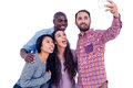 Multi ethnic friends making face while taking selfie happy against white background Stock Photography
