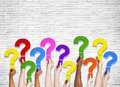 Multi ethnic group of human hands holding question marks Royalty Free Stock Image