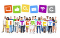 Multi ethnic group of people holding alphabet to form internet and themed images above Stock Photography