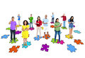 Multi ethnic people standing on jigsaw puzzle group of pictures of pieces wth their electronic devices Royalty Free Stock Photography
