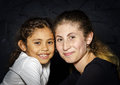 Multi ethnic sisters studio portrait face to face on dark background Stock Photography