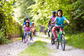 Multi generation african american family on cycle ride in countryside having fun whilst wearing helmets Royalty Free Stock Images