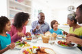Multi generation african american family eating meal at home in kitchen chatting to each other Royalty Free Stock Photo