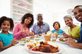 Multi generation african american family eating meal at home looking to camera smiling Royalty Free Stock Photo