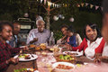 Multi generation family eating dinner in garden, close up Royalty Free Stock Photo
