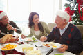 Multi generation family enjoying christmas meal at home looking grandad smiling Stock Images
