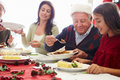 Multi generation family enjoying christmas meal at home putting food on plate Stock Photo