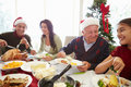 Multi generation family enjoying christmas meal at home sitting around table smiling Stock Images