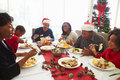 Multi generation family enjoying christmas meal at home sitting down table eating Royalty Free Stock Photos