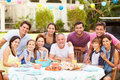Multi generation family enjoying meal in garden together Royalty Free Stock Photography