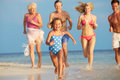 Multi generation family having fun in sea on beach holiday smiling Stock Images