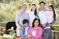 Multi generation family having outdoor barbeque smiling to camera Royalty Free Stock Photos
