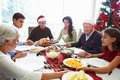 Multi generation family praying before christmas meal sitting around table holding hands Royalty Free Stock Photos