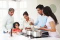 Multi generation indian family cooking meal at home in kitchen talking Royalty Free Stock Images