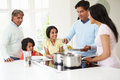 Multi generation indian family cooking meal at home putting food on dish Stock Photography