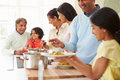 Multi generation indian family cooking meal at home serving food on plates Royalty Free Stock Photos