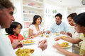 Multi generation indian family eating meal at home chatting to each other Stock Photos