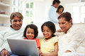 Multi generation indian family with laptop sitting down parents in background Stock Photos