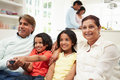 Multi generation indian family sitting on sofa watching tv with parents in background Royalty Free Stock Photos
