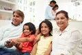 Multi-Generation Indian Family Sitting On Sofa Watching TV Royalty Free Stock Photo