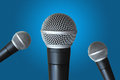 Multi microphones mics ready for speaker announcement against blue background Royalty Free Stock Photos