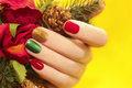 Multicolor manicure with red green and yellow brilliant varnish for the nails on a yellow background with rose and christmas tree Stock Photography