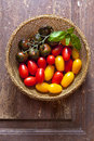 Multicolor red and yellow cherry tomatoes in a wooden basket wit Royalty Free Stock Photo