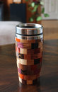 Multicolor travel mug segmented wood turned outer shell made of little squares of a various wood species and with stainless steel Stock Photography