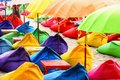 Multicolored bright beach umbrellas, ottomans and tables in the beach cafe. Summer multicolored background. Royalty Free Stock Photo