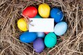 Multicolored eggs with a note in the hay. Mock up, concept easter