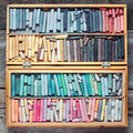 Multicolored pastel crayons in wooden artist box on table. Royalty Free Stock Photo
