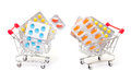 Multicolored pills packs in shopping cart on white background Royalty Free Stock Photos