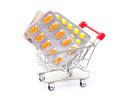 Multicolored pills packs in shopping cart on white background Stock Photography
