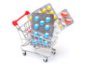 Multicolored pills packs in shopping cart on white background Stock Images