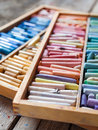 Multicolored professional artistic pastel crayons in open box set of wooden on table selective focus Stock Photo