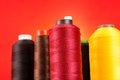 Multicolored spools of thread against a bright orange background Stock Image
