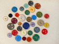 Multicoloured buttons on beige fabric suitable as background Royalty Free Stock Image