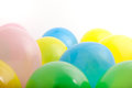 Multicoloured party balloons in green blue yellow and pink in a random scatter on a white background with copyspace Stock Photos