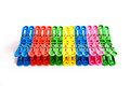 Multicoloured plastic clothes pegs on a white background Royalty Free Stock Photography