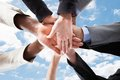 Multiethnic businesspeople s hands on top of each other closeup business people symbolizing unity against sky Stock Photos