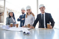 Multiethnic contractors in formal wear working with blueprints at construction area Royalty Free Stock Photo