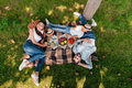 Multiethnic family eating and drinking while resting on plaid at picnic