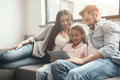 Multiethnic family using digital tablet while sitting on sofa at home
