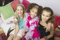 Multiethnic girls sitting on trendy sofa at slumber party portrait of three with arms around a Royalty Free Stock Photos
