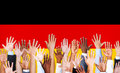 Multiethnic Hands Raised and German Flag Royalty Free Stock Photo