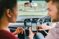 Multiethnic lover couple use navigation system on smartphone in car. Mobile phone application or crowdsourcing taxi app service