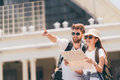 Multiethnic traveler couple using generic local map together on sunny day. Honeymoon trip, backpacker tourist, Asia tourism Royalty Free Stock Photo