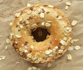 Multigrain bagel covered in oats and seeds on crinkled brown paper Royalty Free Stock Photo