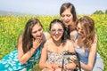 Multiracial girlfriends at countryside picnic watching photos Royalty Free Stock Photo