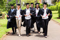 Multiracial graduates walking Stock Photos